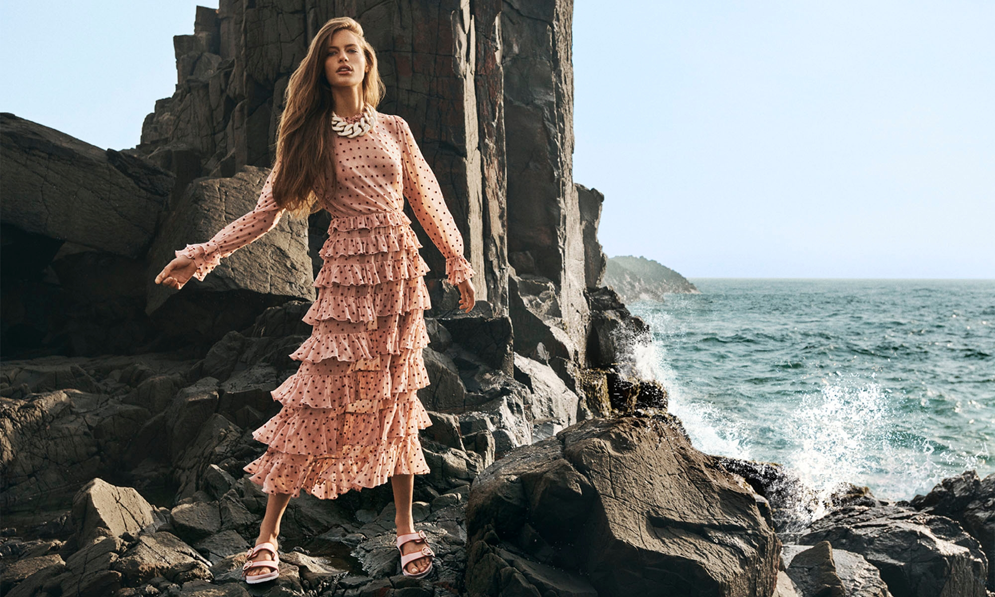 WOMAN STANDING ON THE ROCKS BY THE OCEAN WEARING8135DWAV Wavelength Ruffle Midi, BalletBerry Dot, 3158S20 Satin Slide, Dusty Pink,  3171S20 Resin Link Necklace