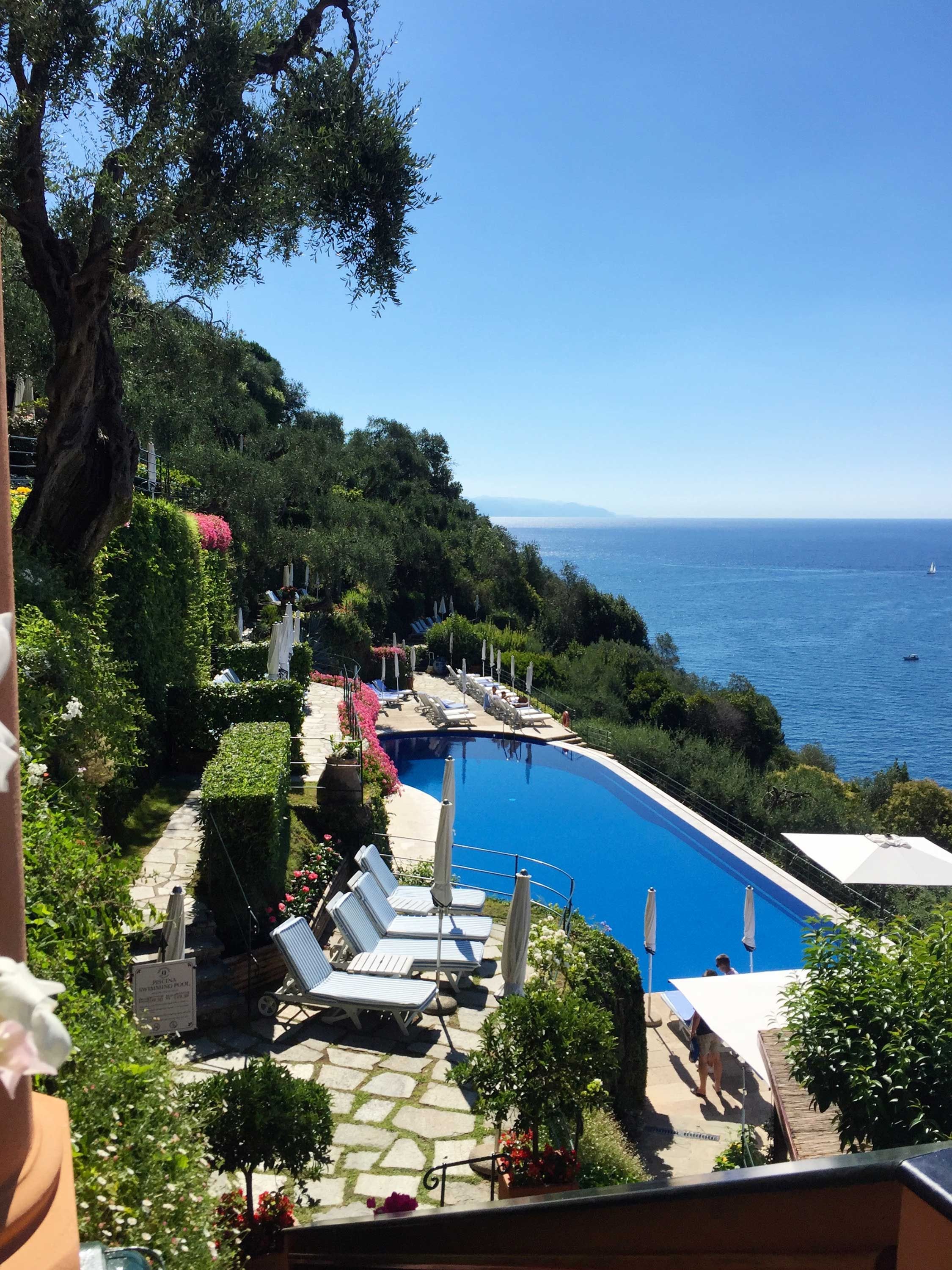 The pool at Hotel Splendido sits amongst thick greenery on the side of a mountain and overlooks the deep blue Mediterranean