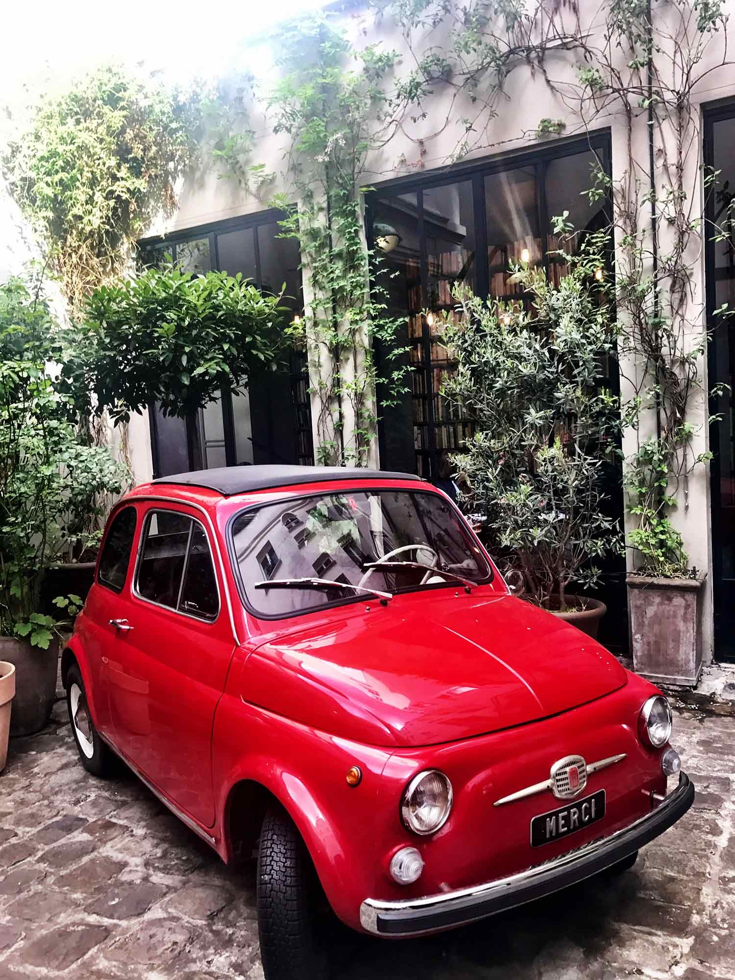 A vintage red Fiat sits in a courtyard surrounded by vines