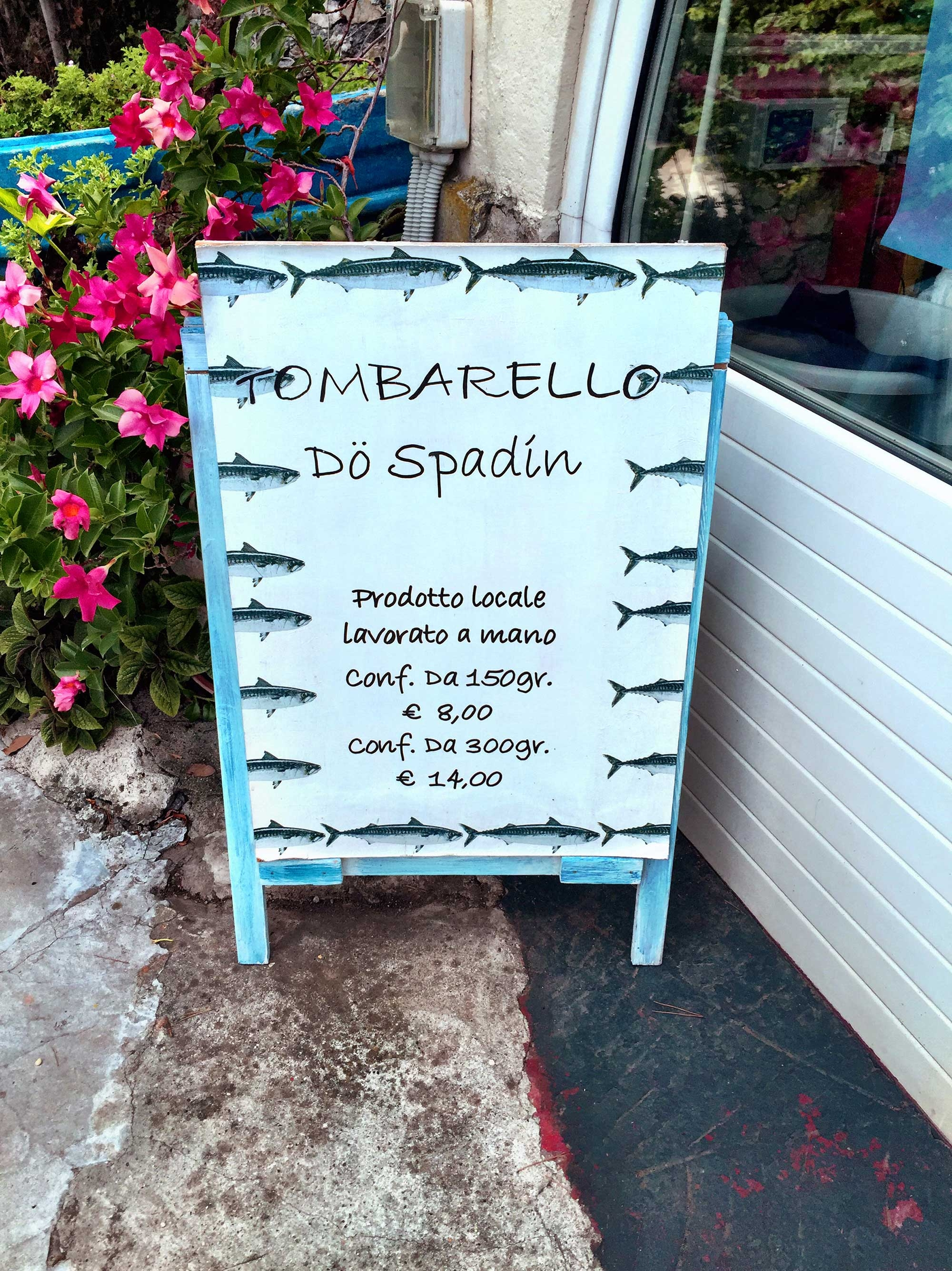 A blue sign sits outside a restaurant advertising a seafood lunch in Italian