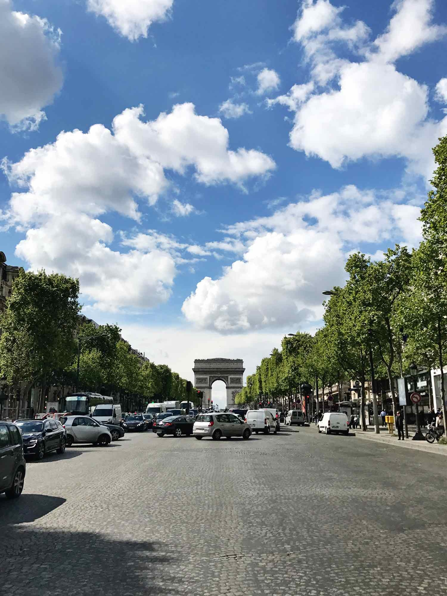 The road to the Arc De Triomphe is filled with cars and lined with perfectly planted trees