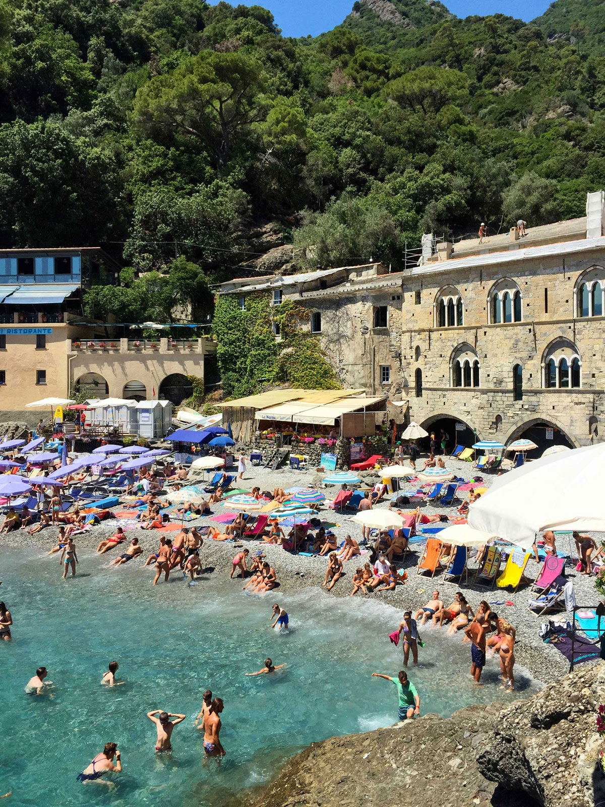 The small beach of San Fruttuoso is filled with beach umbrellas and people sunbathing, swimming and chatting