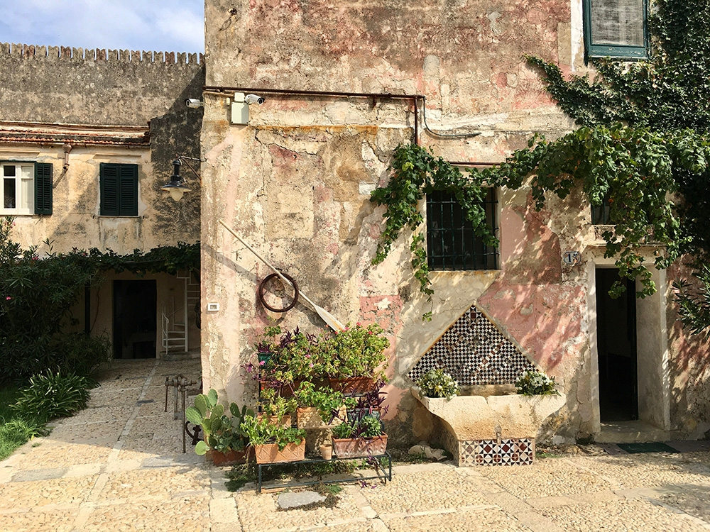 Old buildings and greenery line the streets of Scopello