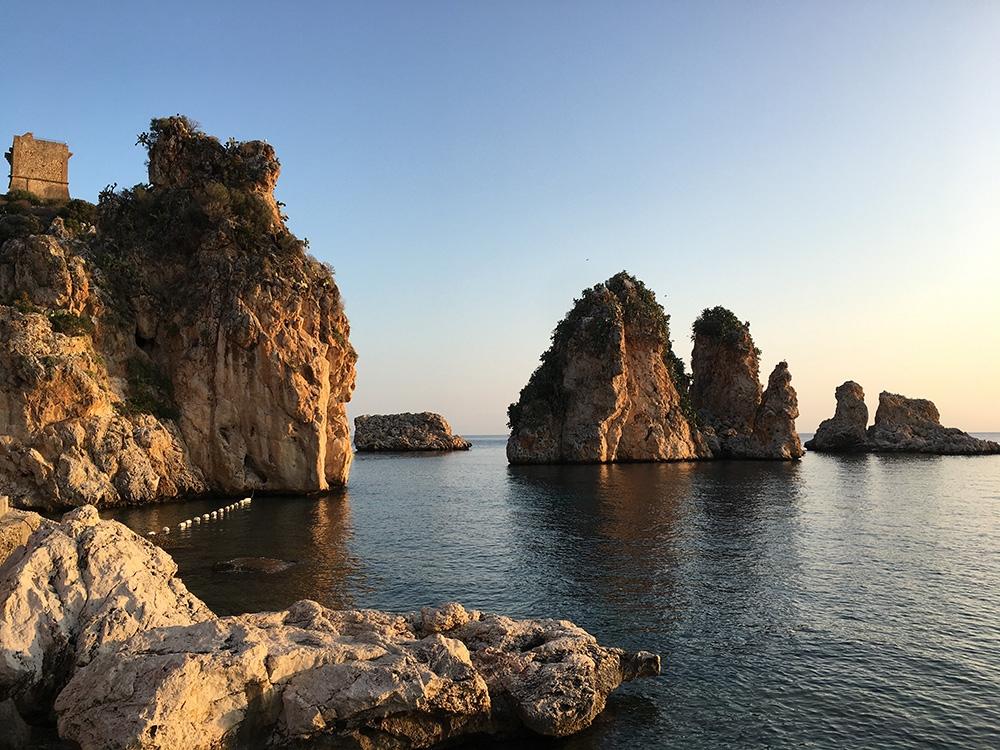 Golden hour over Faraglioni rock formations