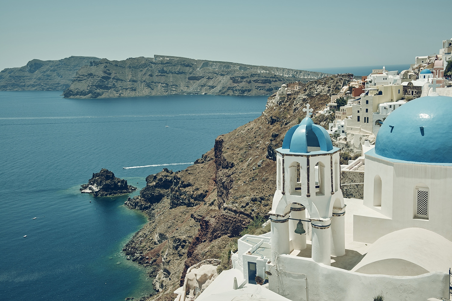 A cliffside white and blue chapel with views of the surrounding mountains and ocean