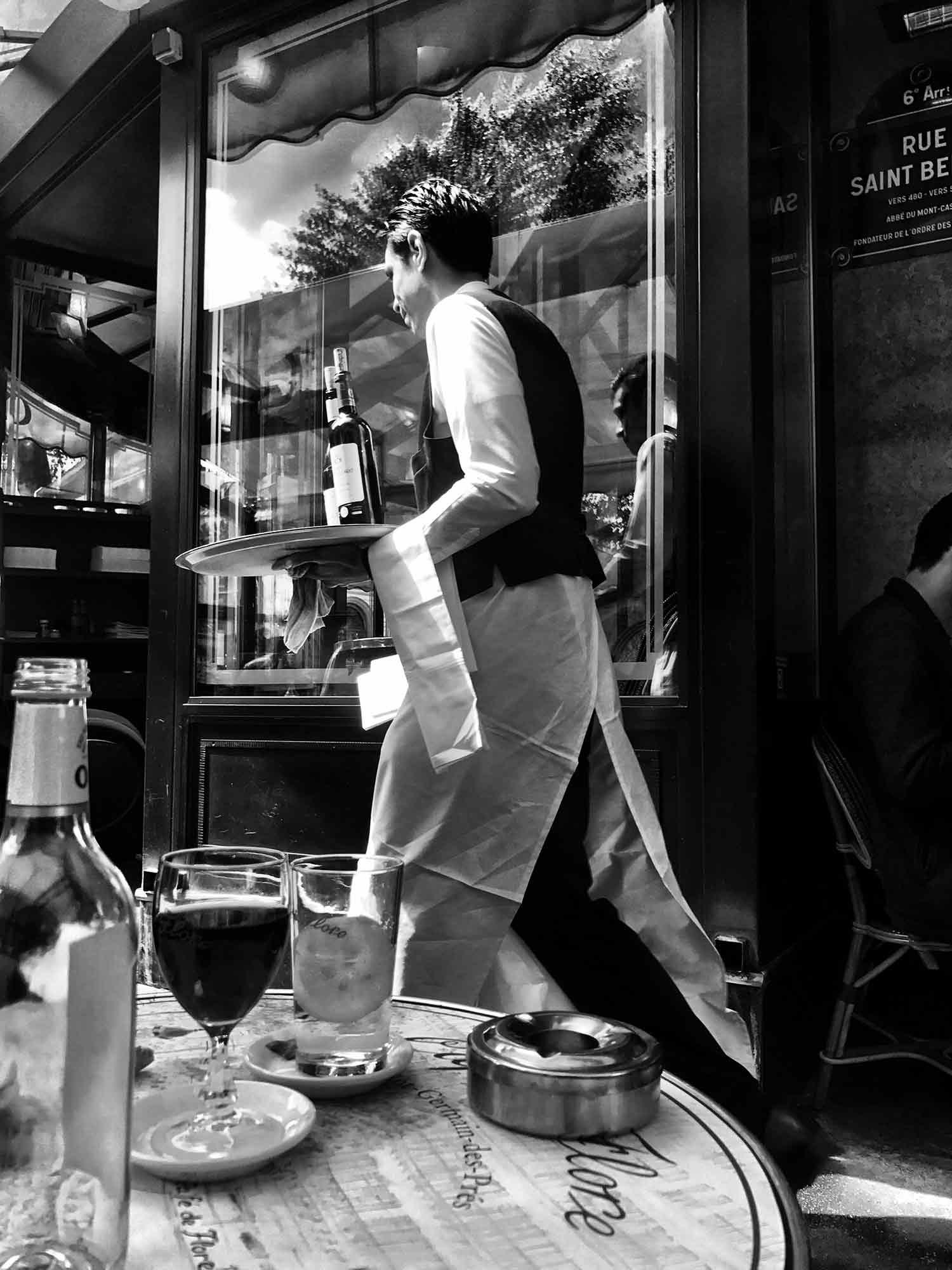A black and white candid image of a waiter at Café de Flore. December 2018