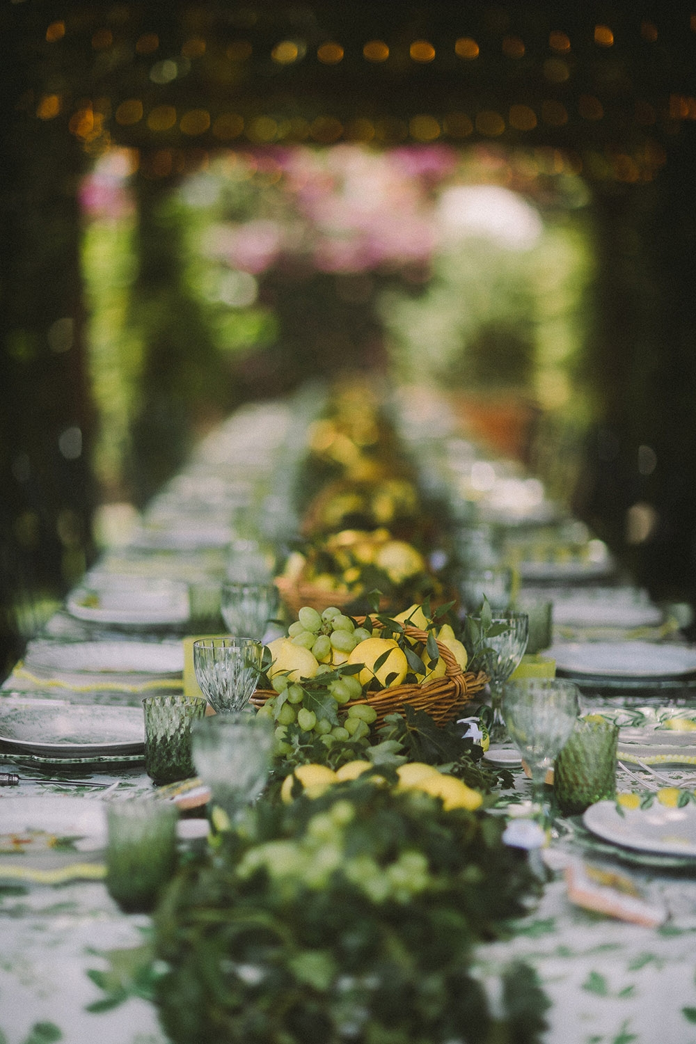 A long rectangular table underneath a lemon trellis has been set for lunch with wicker baskets of lemons and grapes as the centerpiece, light green crystal glasses and patterned plate settings.