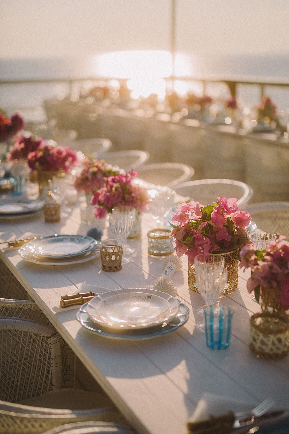 The table setting for a sunset dinner. Vases of flowers run down the centre and blue and white tableware has been set at each place setting.