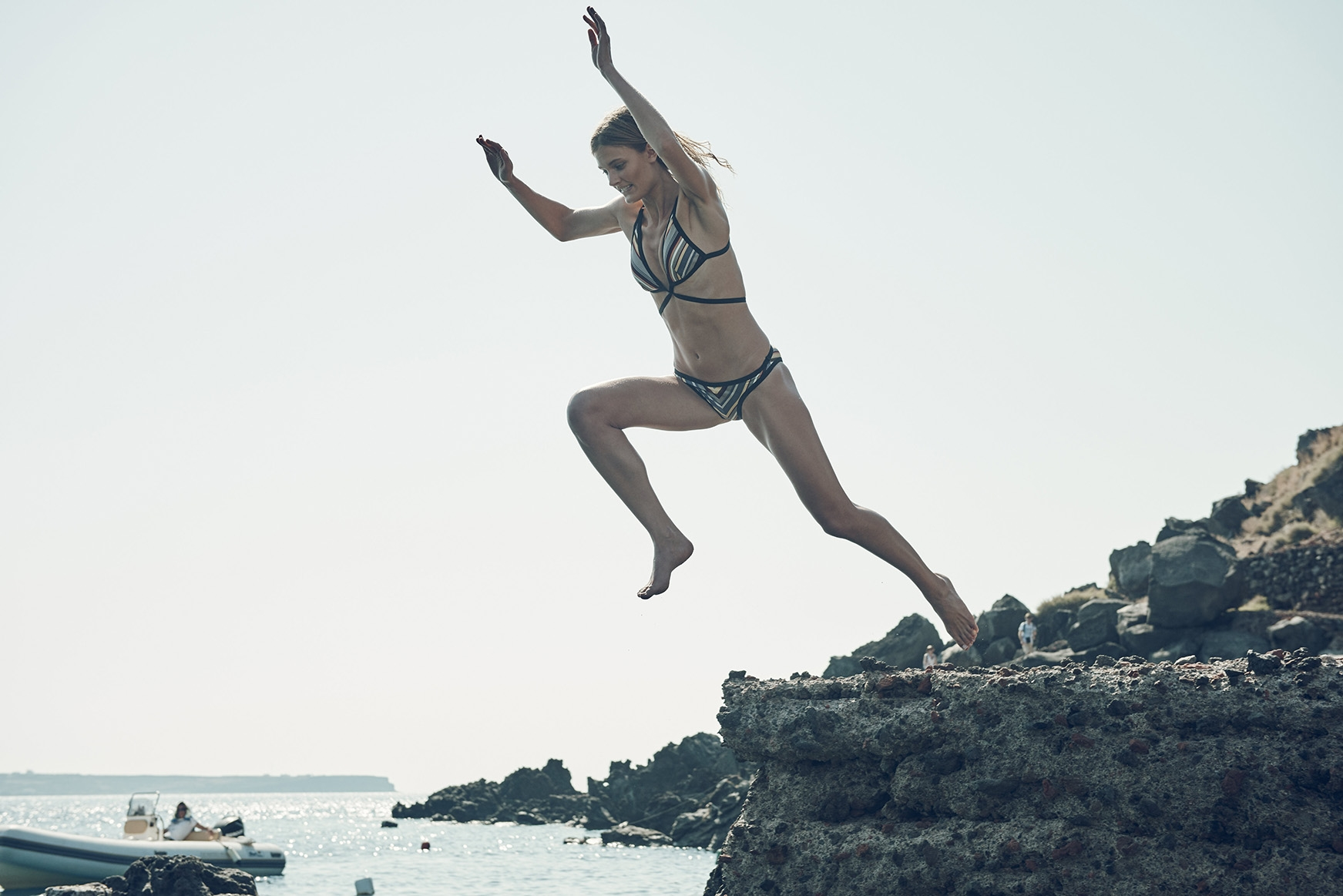 A behind the scenes shot of our model jumping off a rock and into the water
