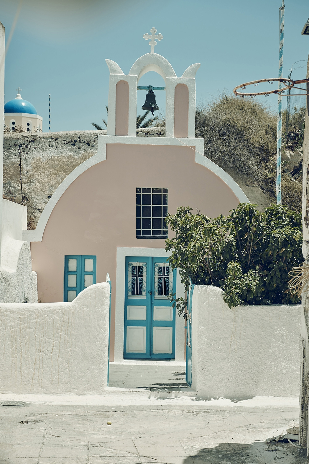 A pastel pink church with bright blue doors and white trims