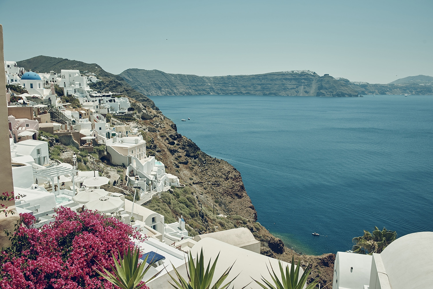 White buildings line the cliffside and look down to the deep blue sea below
