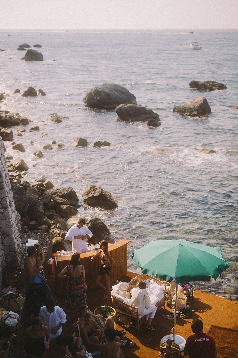 A pop-up bar on the shoreline, surrounded by men and women lounging by the water.