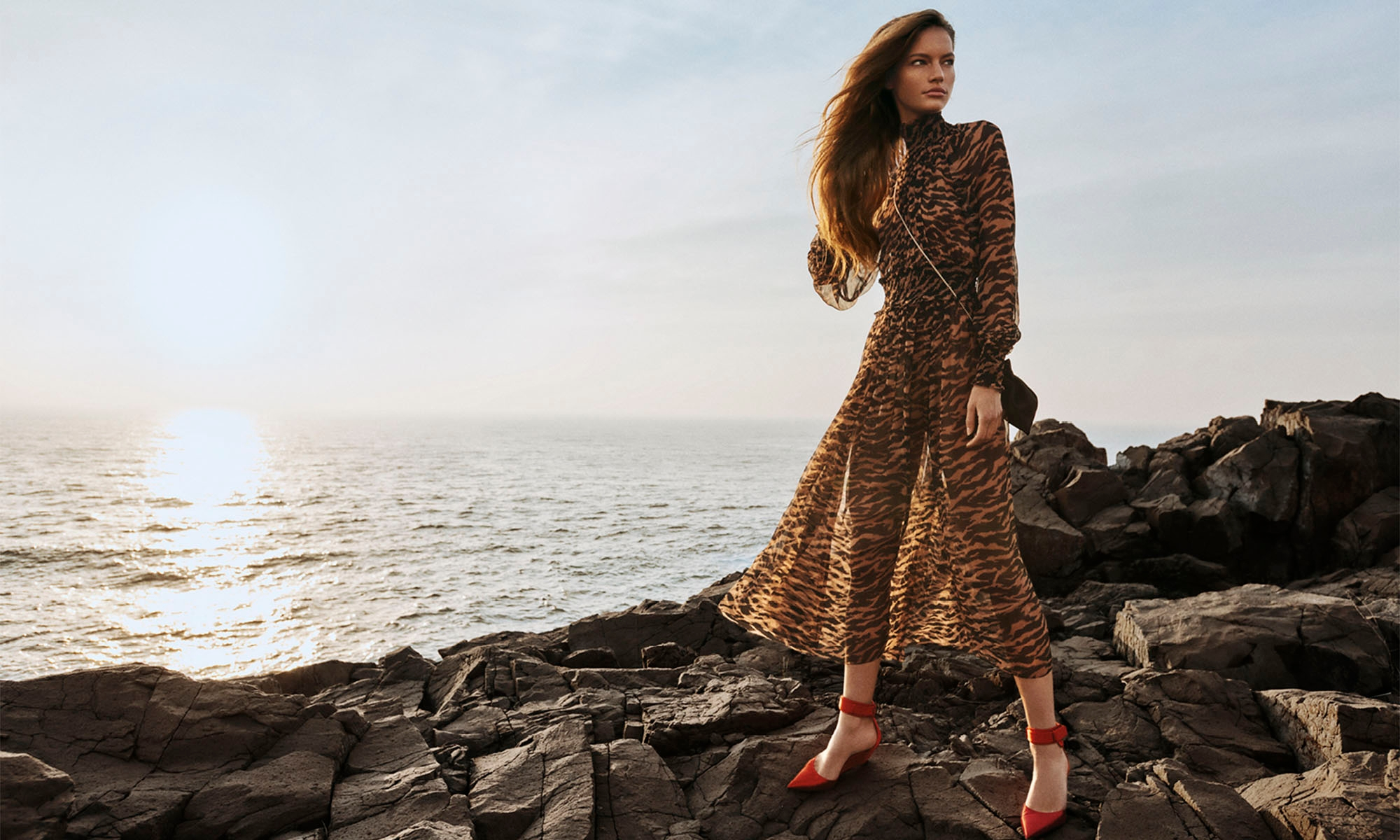 WOMAN STANDING ON THE ROCKS BY THE OCEAN WEARING 8125DWAV Wavelength Shirred Midi, Sumatran Stripe, 3143S20 Mini Pouch, Black, 3104S20 Satin Surf Wedge, Ruby