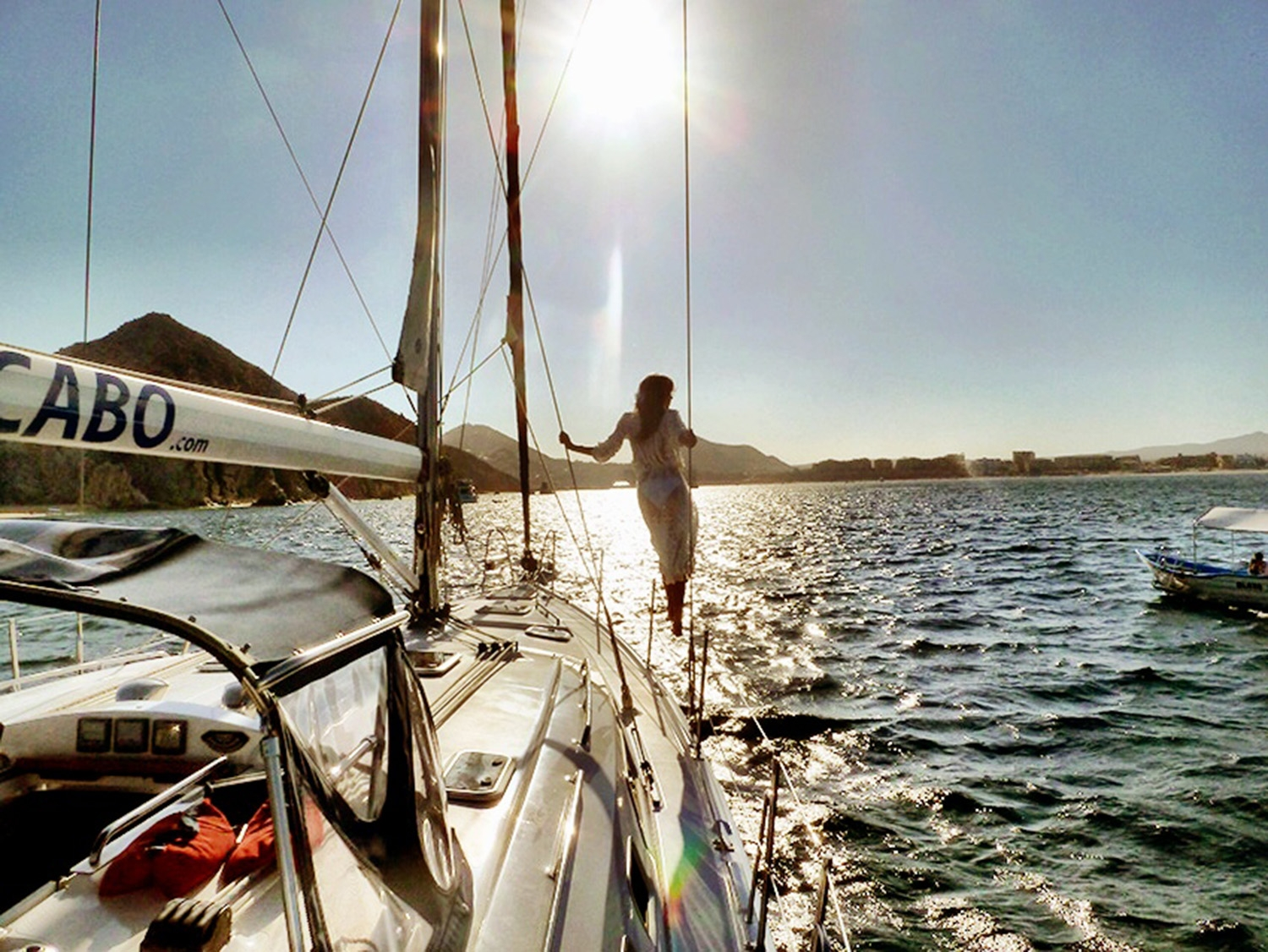The sun shines down over the mountains and onto the ocean, where our model stands at the bow of the yacht