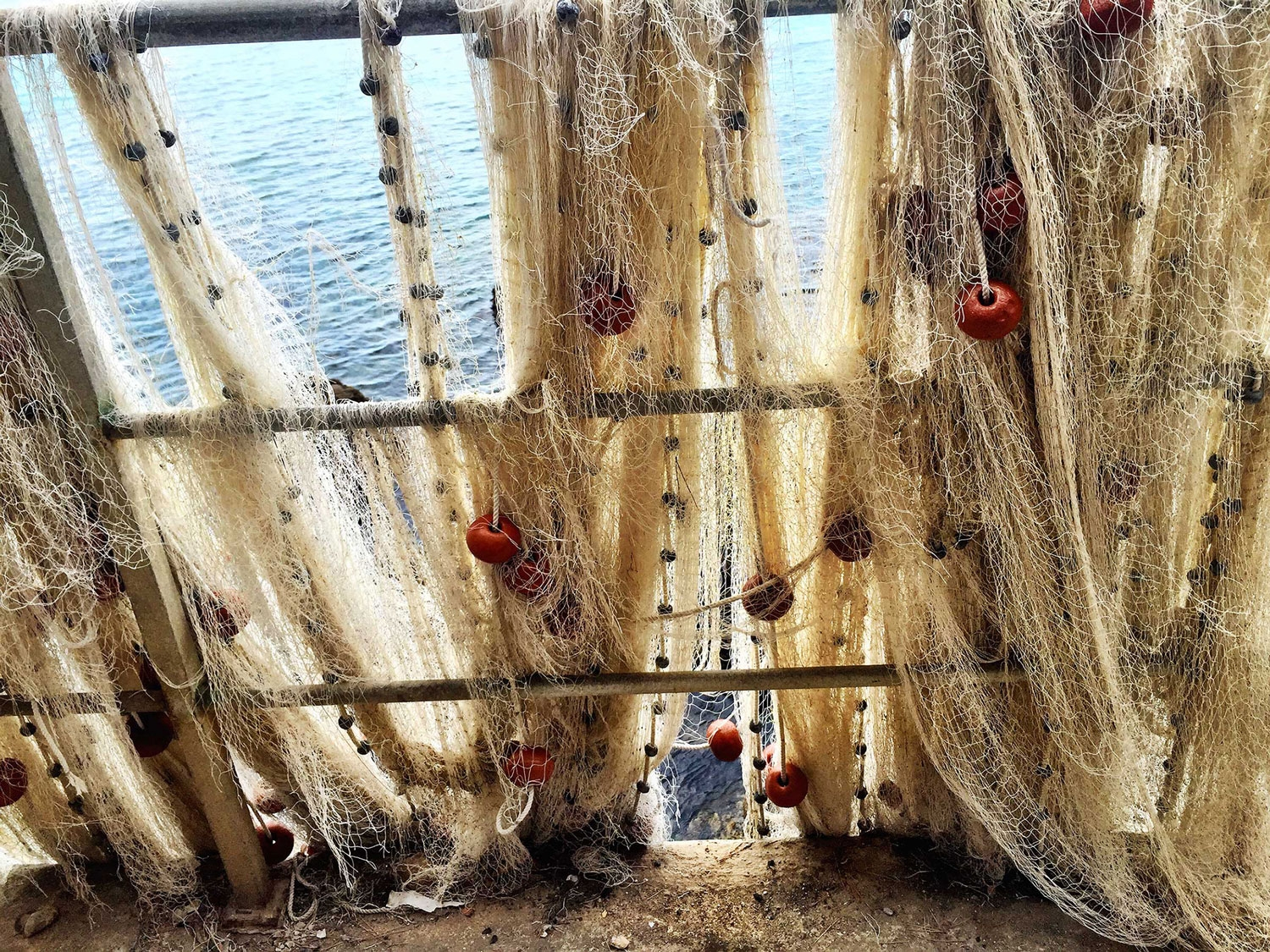 Fishing nets hung across metal railings by the ocean at Camogli