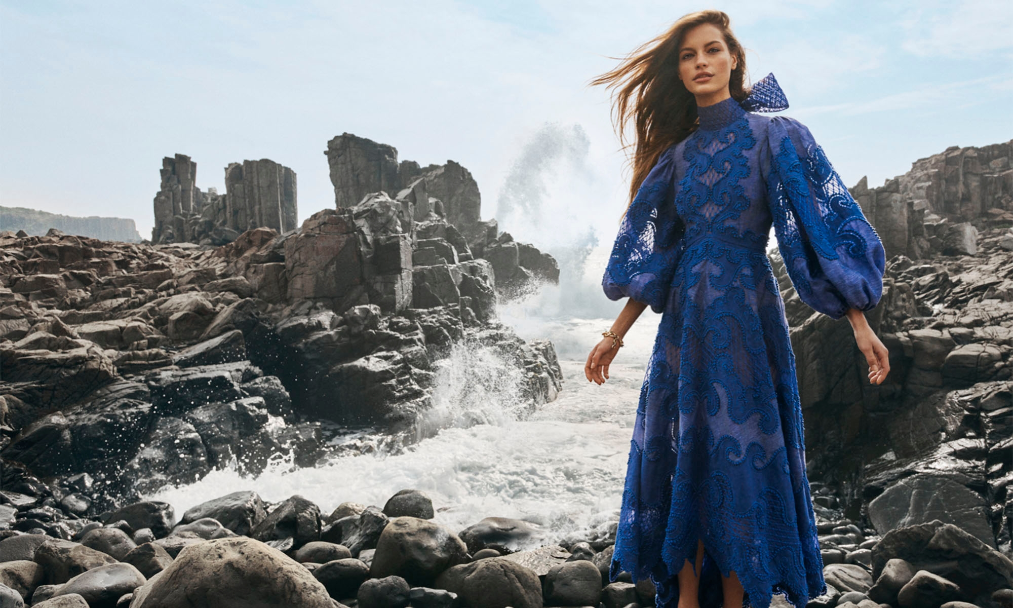 WOMAN STANDING ON THE ROCKS BY THE OCEAN WEARING 7794DBRI Brightside Knot Embroidered Gown, Blue