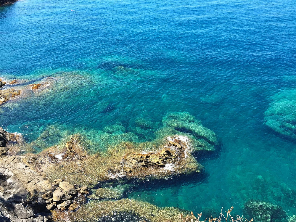 Large rocks sit in the clear water of the Cinque Terre coastline