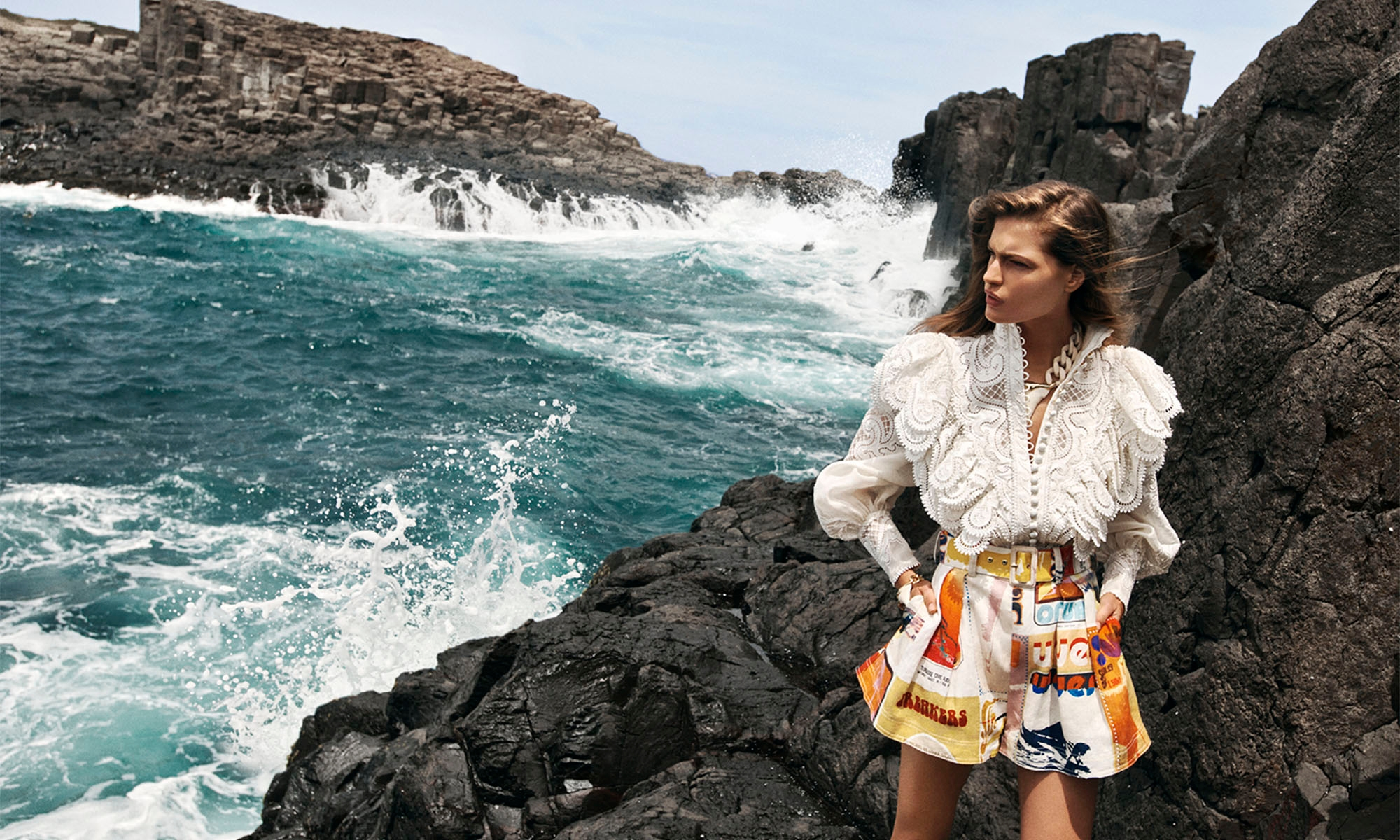 WOMAN STANDING ON THE ROCKS BY THE OCEAN WEARING 7802TGLA Glassy Wave Blouse, Ivory, 5789ABRI Brightside Flared Shorts, Golden Poster Print