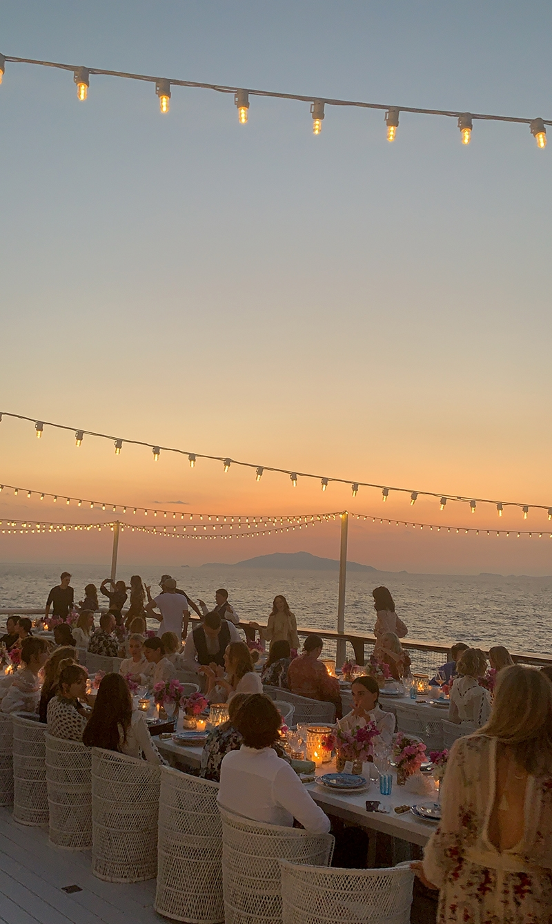 Two long tables of guests dine at sunset at Il Riccio, a seaside restaurant, with fairy lights strung overhead and candles lit on the tables.