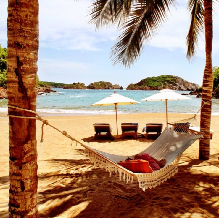 A hammock hangs between two palm trees behind sun loungers and umbrellas on the beach