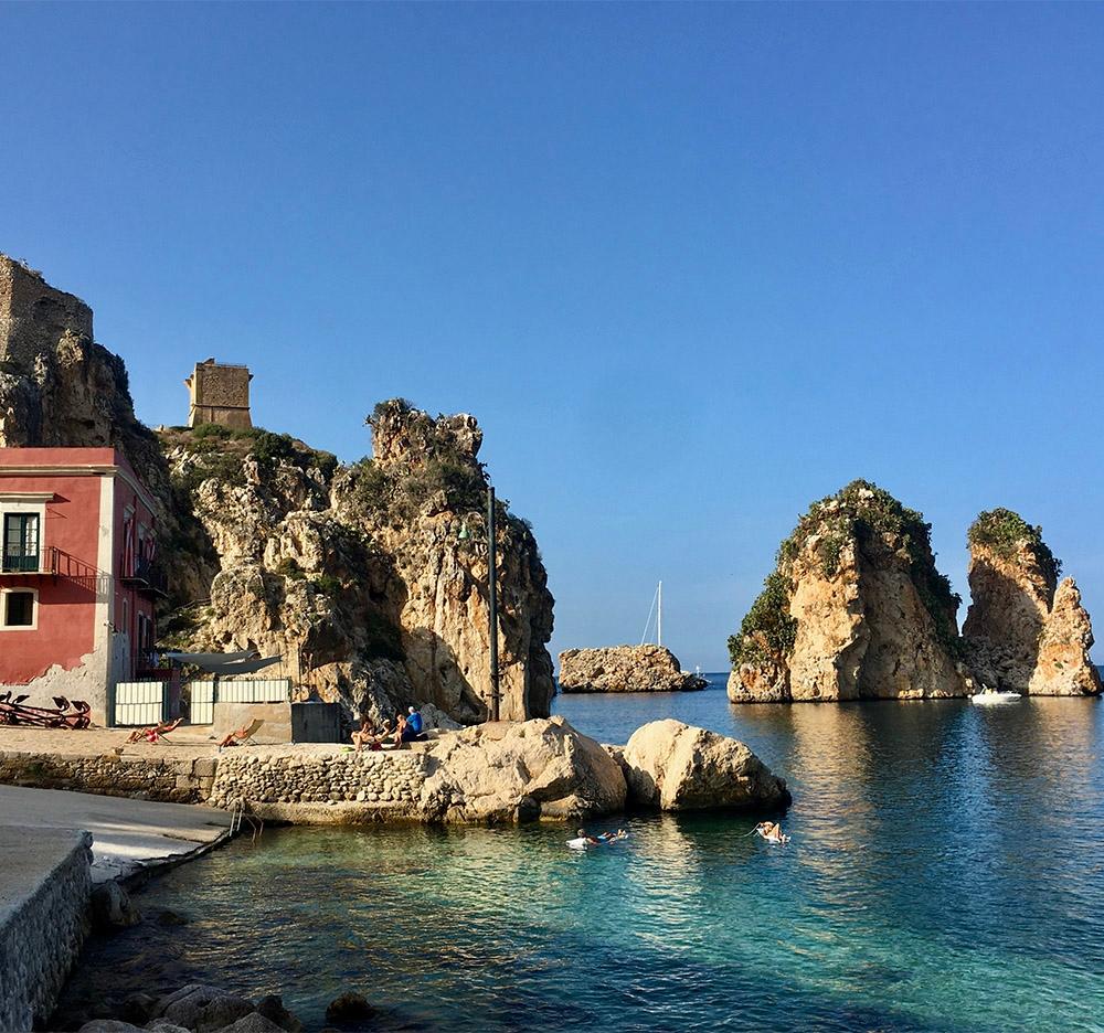 Faraglioni rocks sit along the coast of Scopello