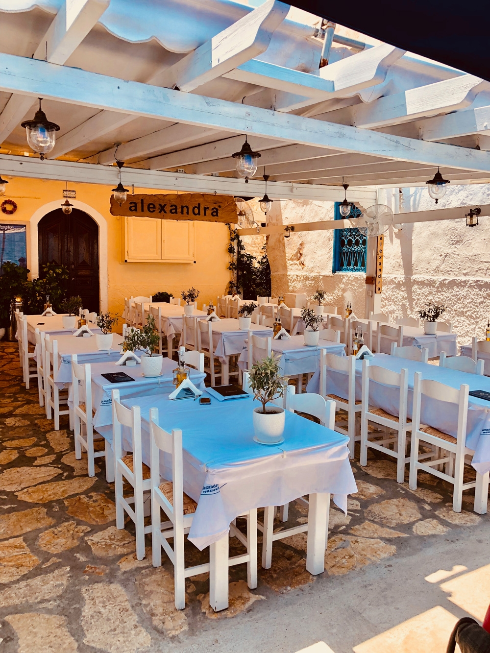 Alexandra Restaurant is a pastel yellow building with stone floors and white outdoor table seating