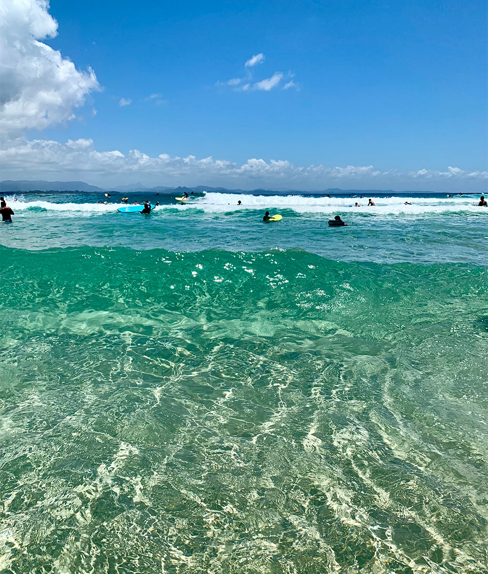 The blue waters of Byron Bay filled with surfers on a bright, sunny day