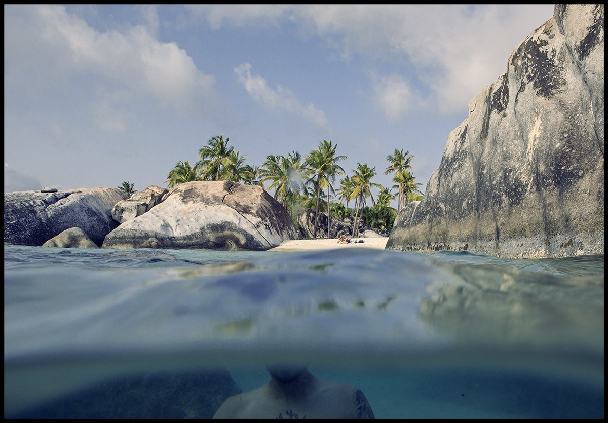 In the deep blue water looking back at the large rocks and tall palm trees of the coast