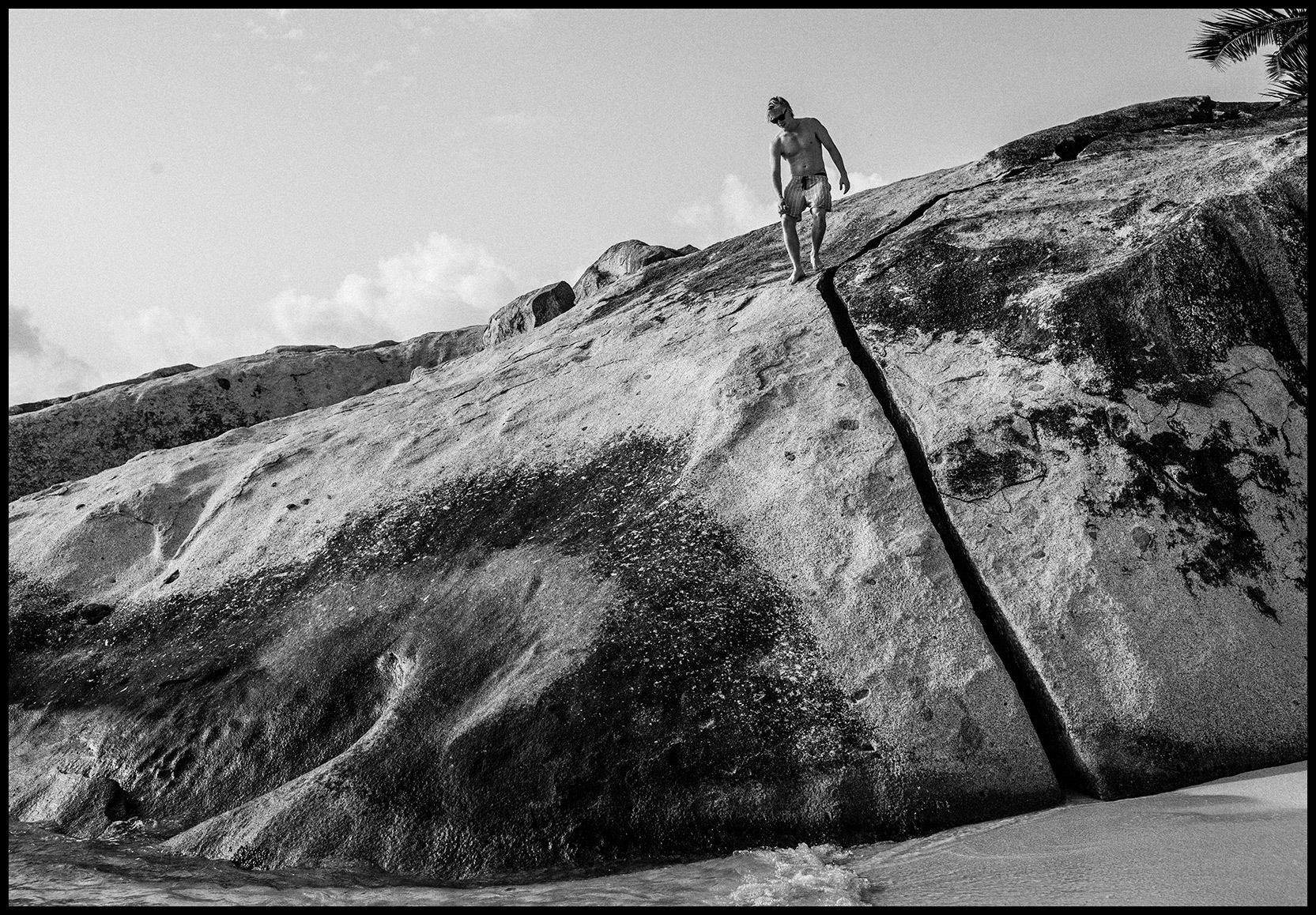 A person standing on a large rock formation on Virgin Gorda's coast