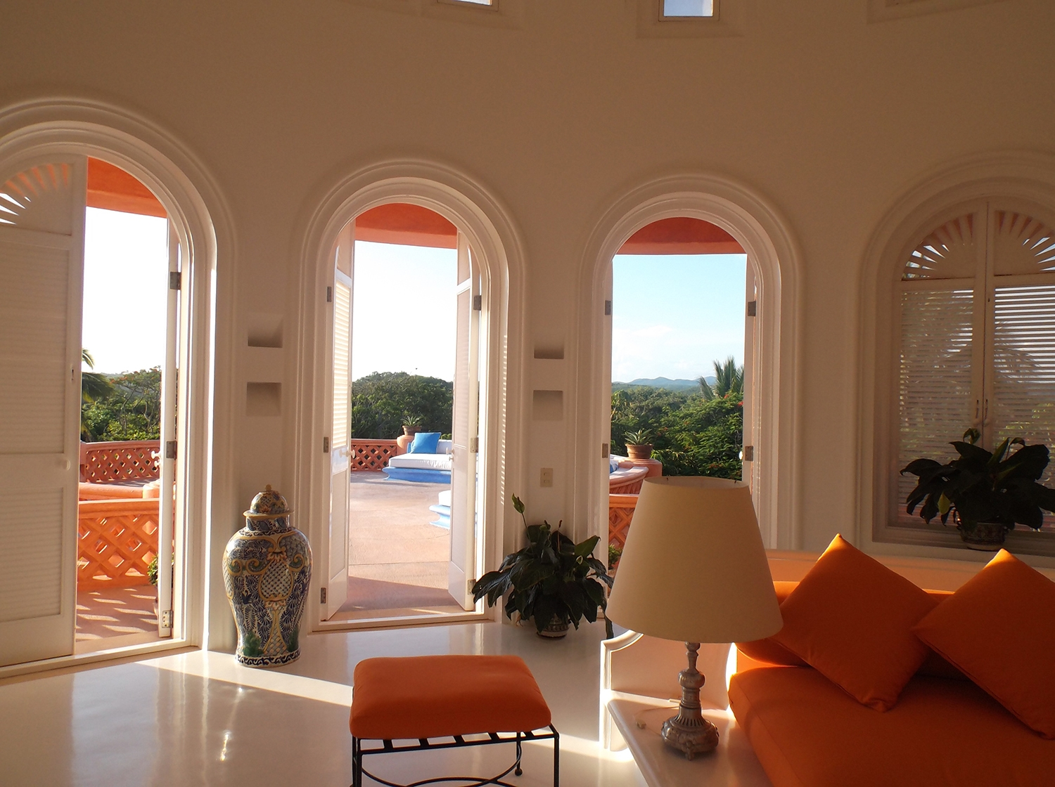 Orange interiors and large arch doorways lead out to a balcony at Casa Playa