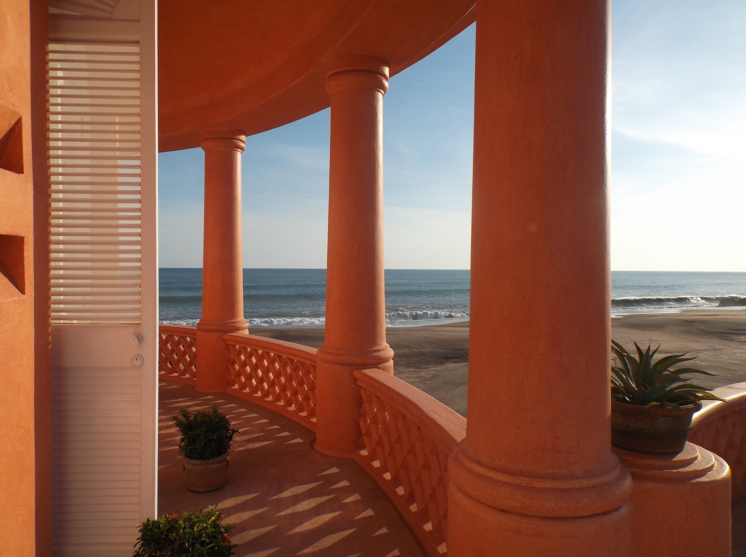 The view of the nearby ocean and large columns from the balcony at Casa Playa