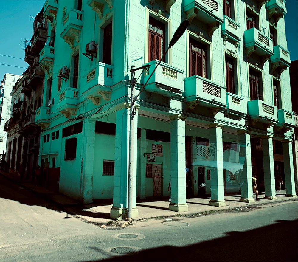 A three story, mint green building in downtown Havana