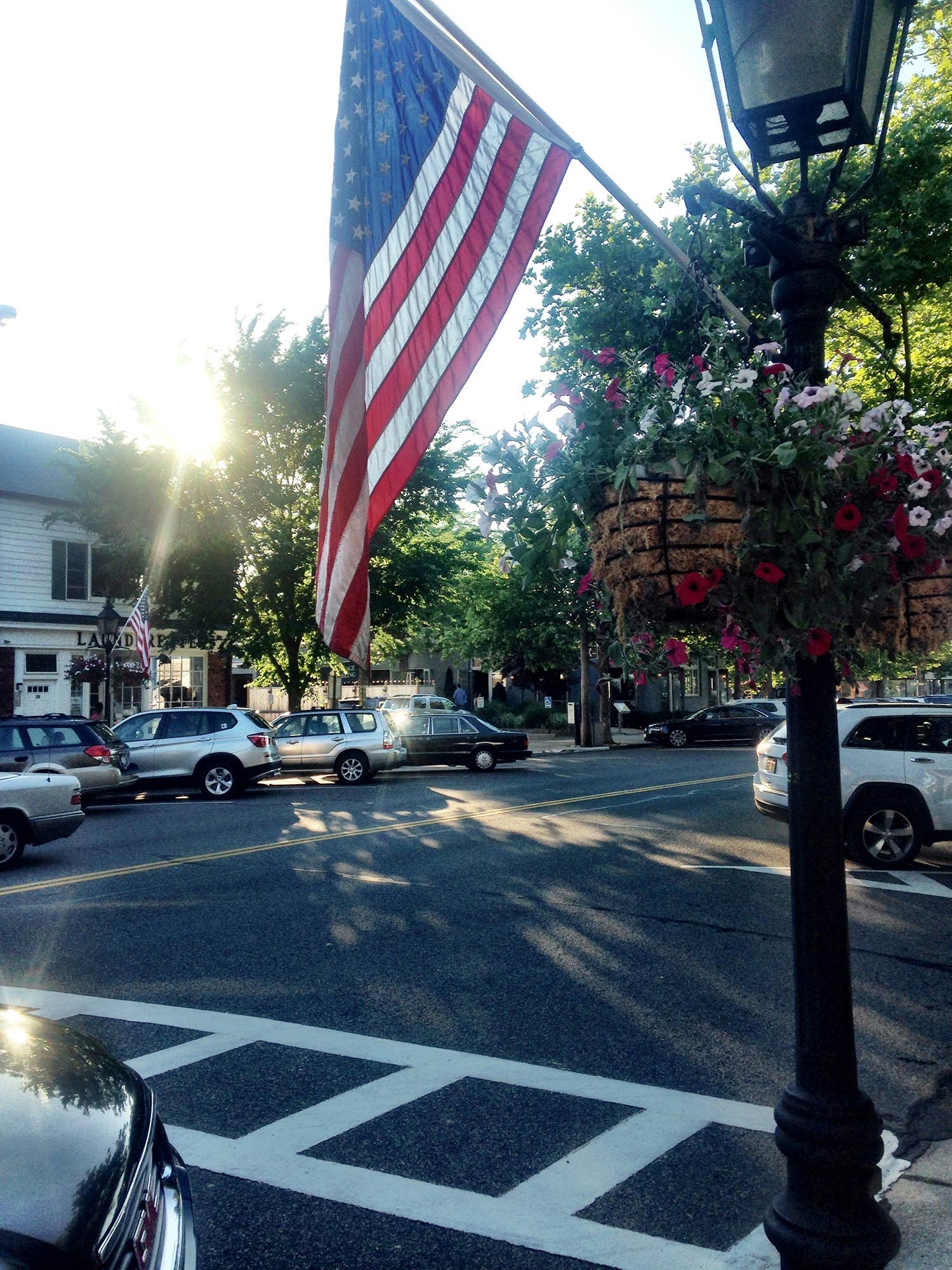 The American flag hanging from a pole on a street in East Hampton
