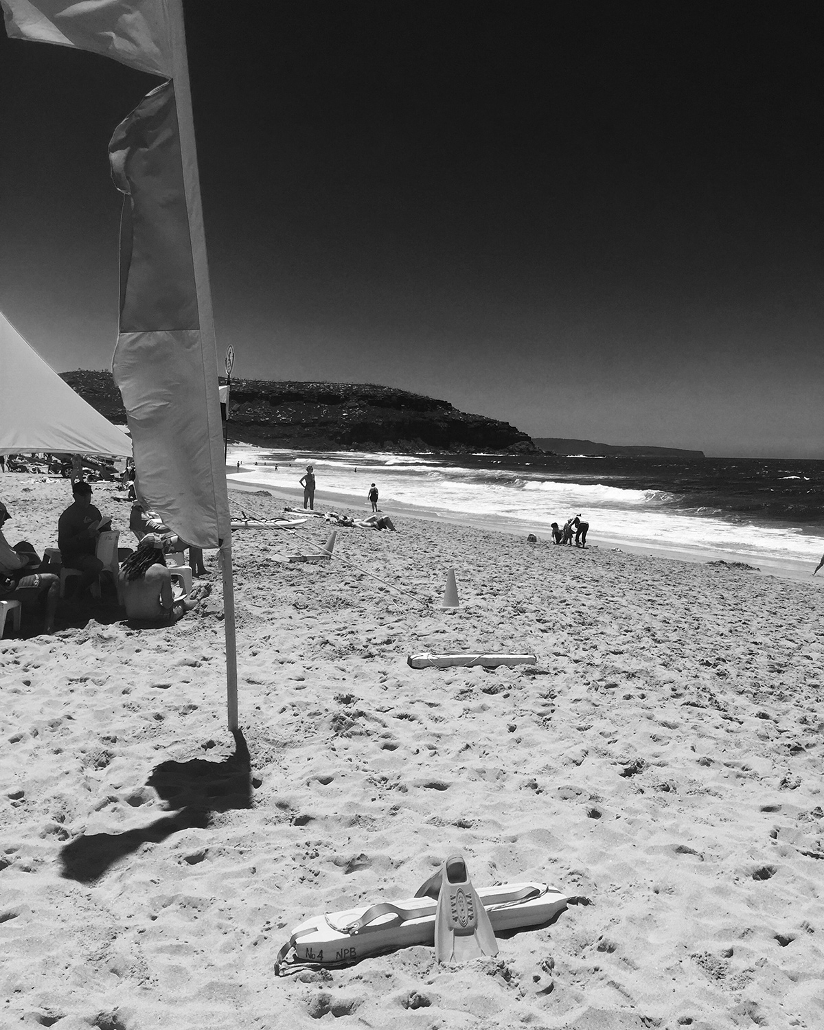 A black and white image of the Surf Lifesaving flags and groups of people sitting along the beach
