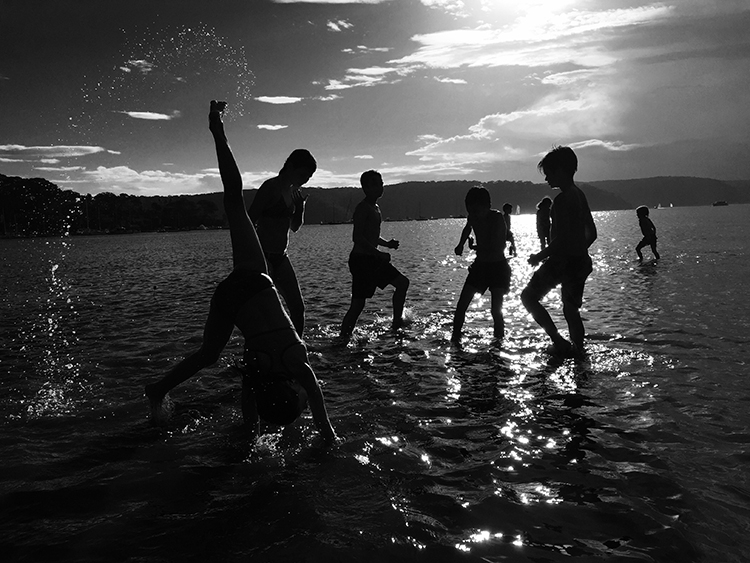 A black and white image of children playing on the shoreline of Palm Beach