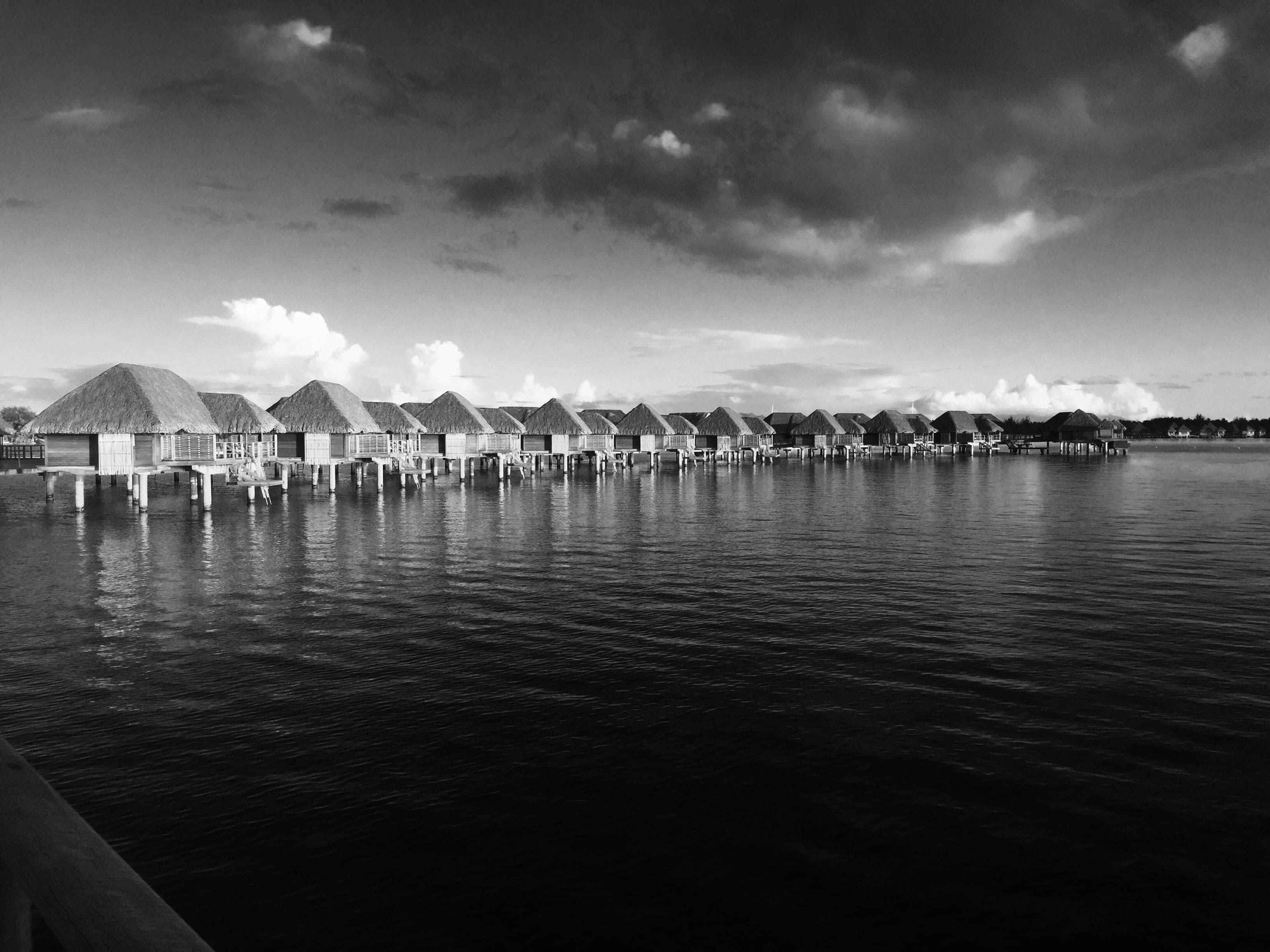 A black and white image of a line of villas expanding out across the ocean