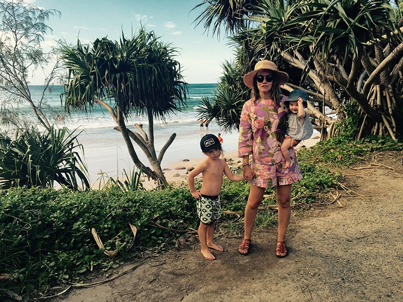 Marnie and her children, Costa and Teddy Jean, stand together in front of the Byron coastline