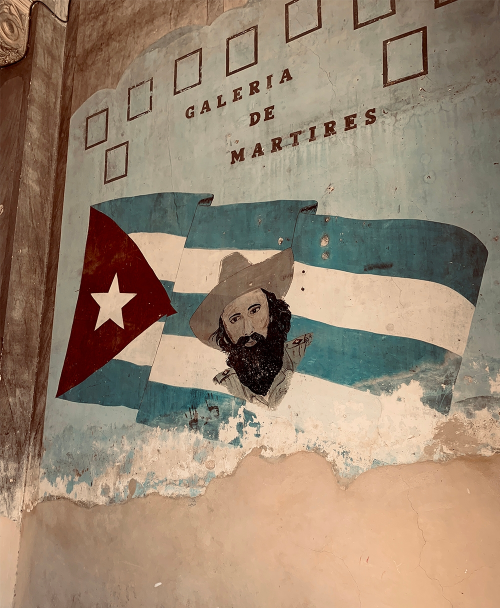 """A wall in the Galeria De Martires with a painting of the Cuban flag, a man's face and """"Galeria De Martires"""""""