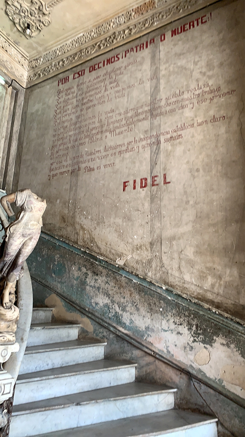 An ascending staircase in the Galeria De Martires with red Spanish writing on the wall