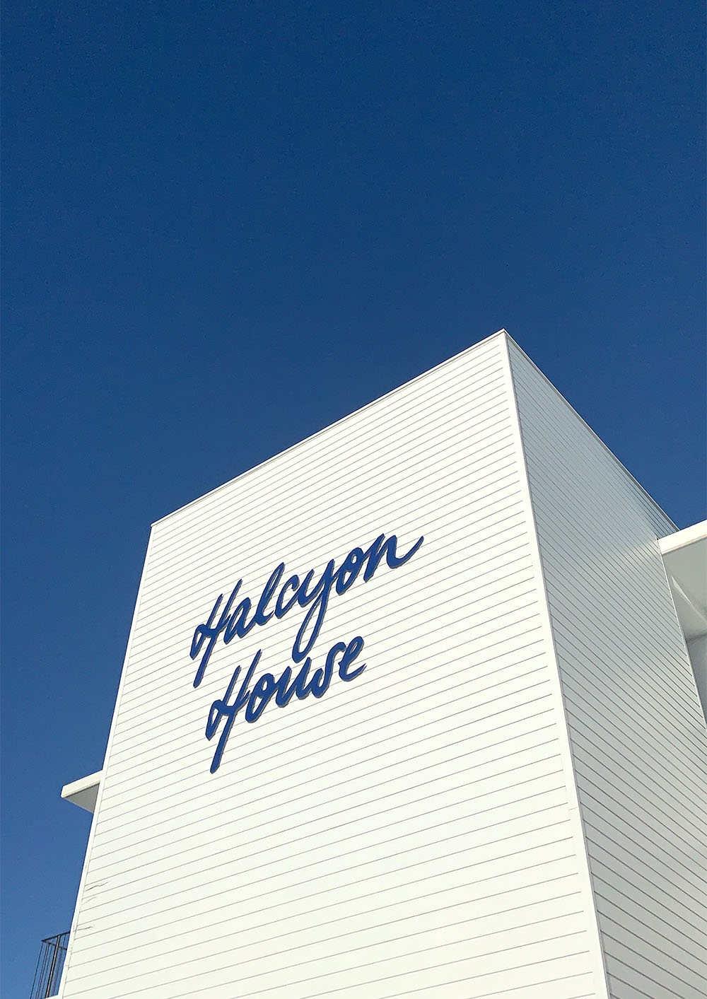 """A bright white exterior wall at the hotel with deep blue """"Halcyon House"""" branding"""
