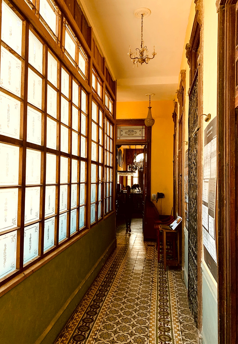 A hallway lined with windows and patterned floor tiles