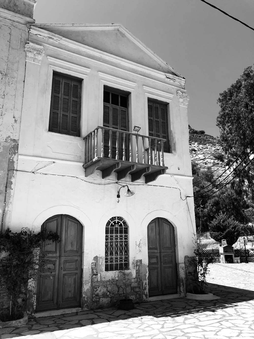 A black and white image of a Neoclassical Greek home with arched doorways and rectangle windows