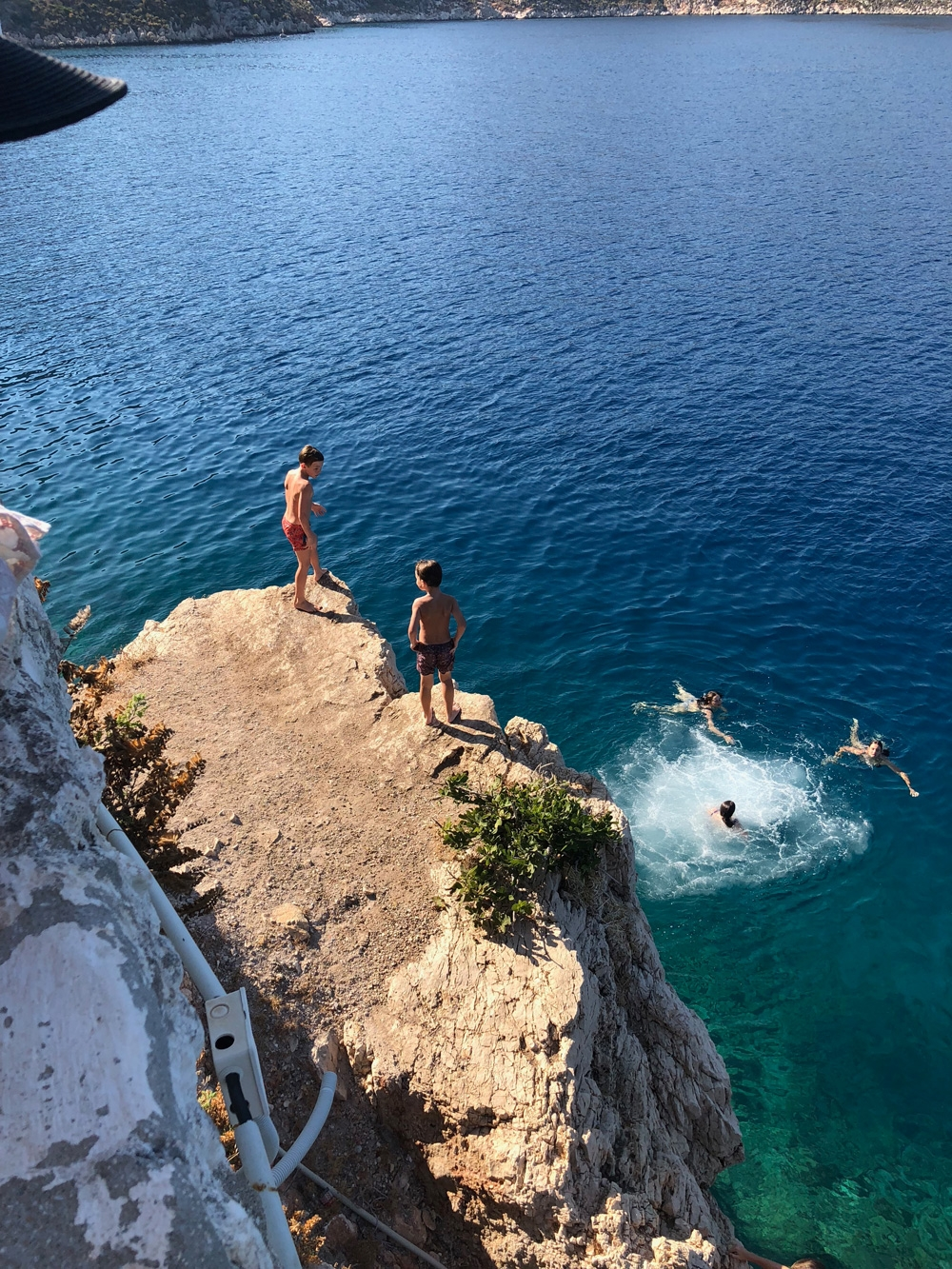 Children enjoying the sunshine and cliff diving into the deep blue ocean