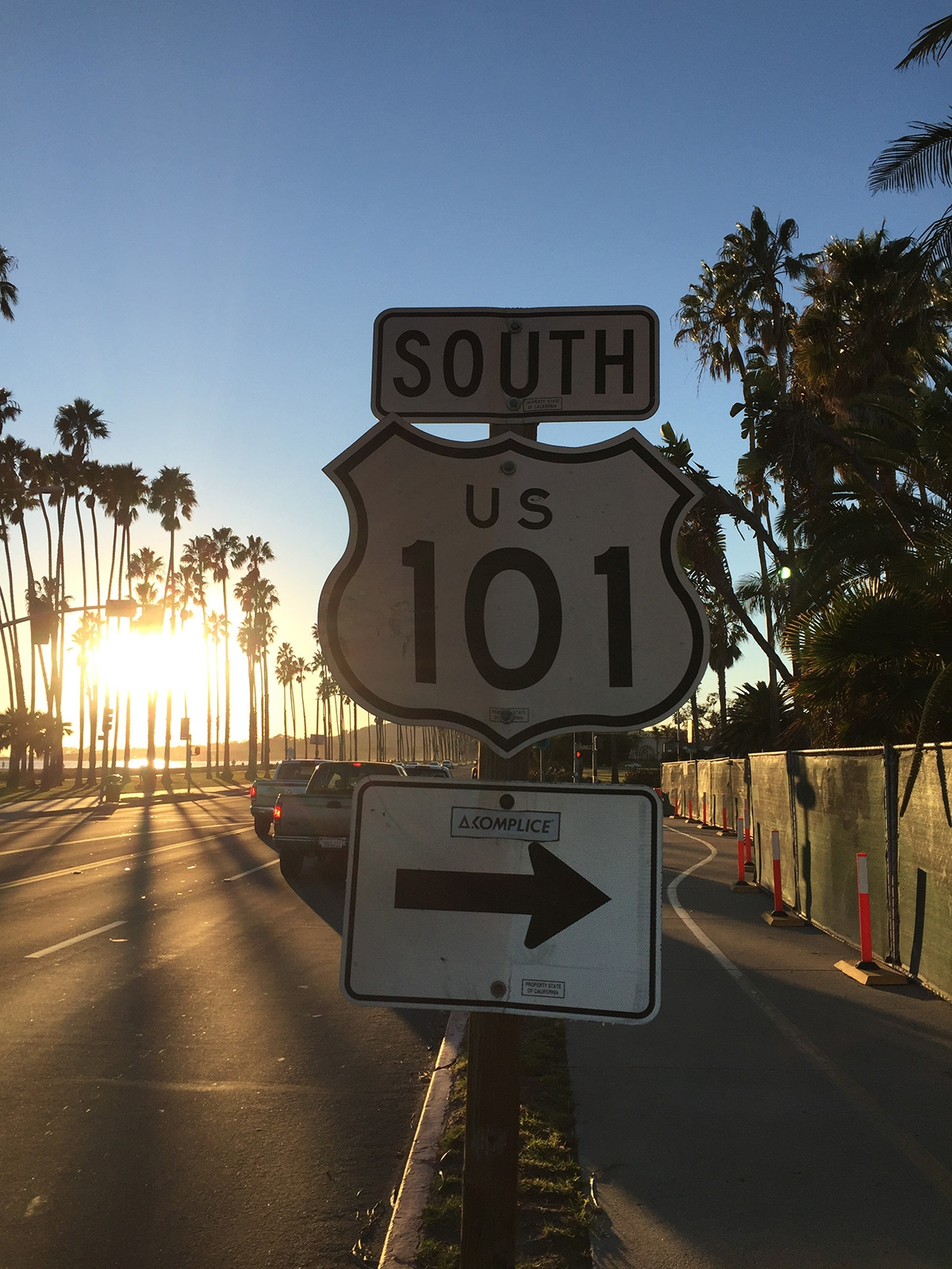 A road sign for South Route 101 and the sun setting behind tall palm trees