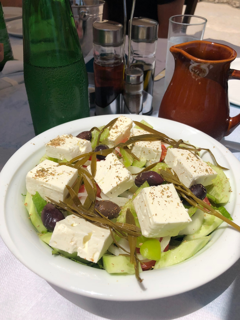 A plate of Greek salad consists of thick cut feta, cucumber, olives and other traditional ingredients
