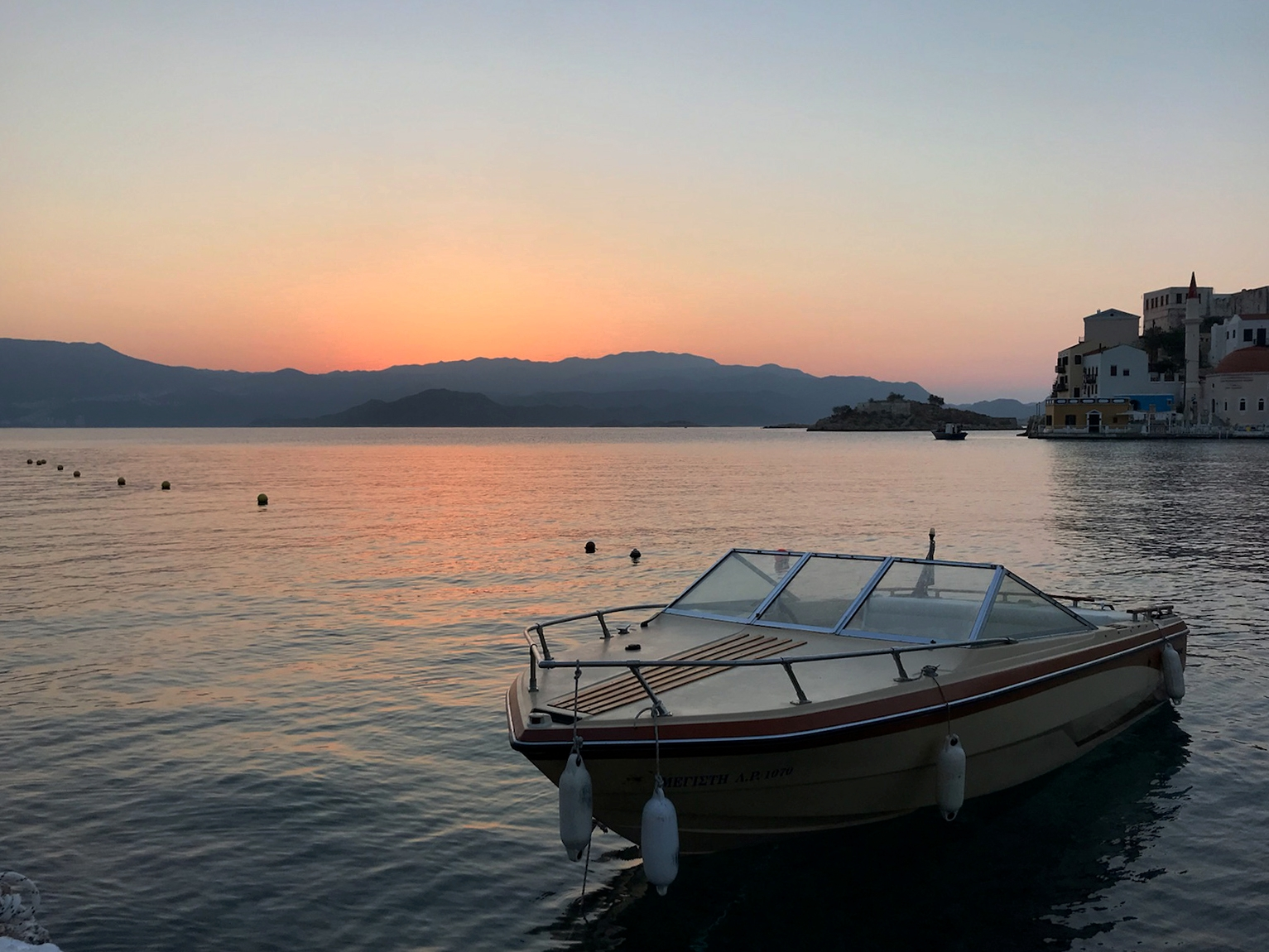 A small speedboat is anchored on tranquil waters as the sun sets behind the mountains