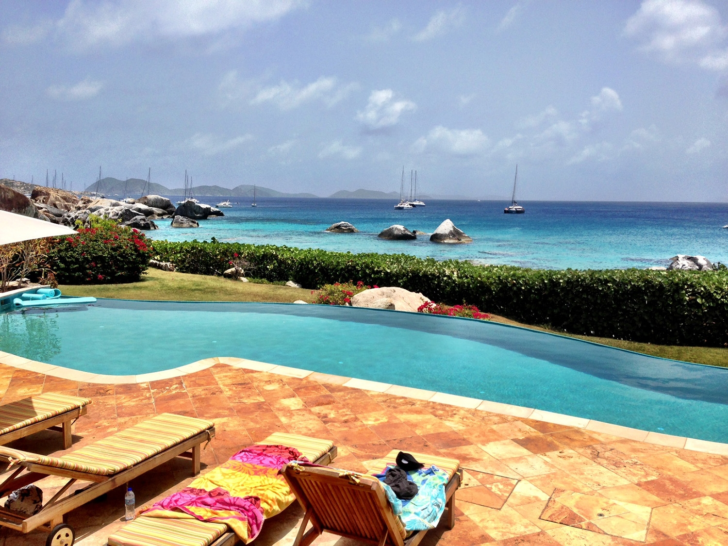 Sitting poolside with a grassy patch separating the boat filled ocean from the villa