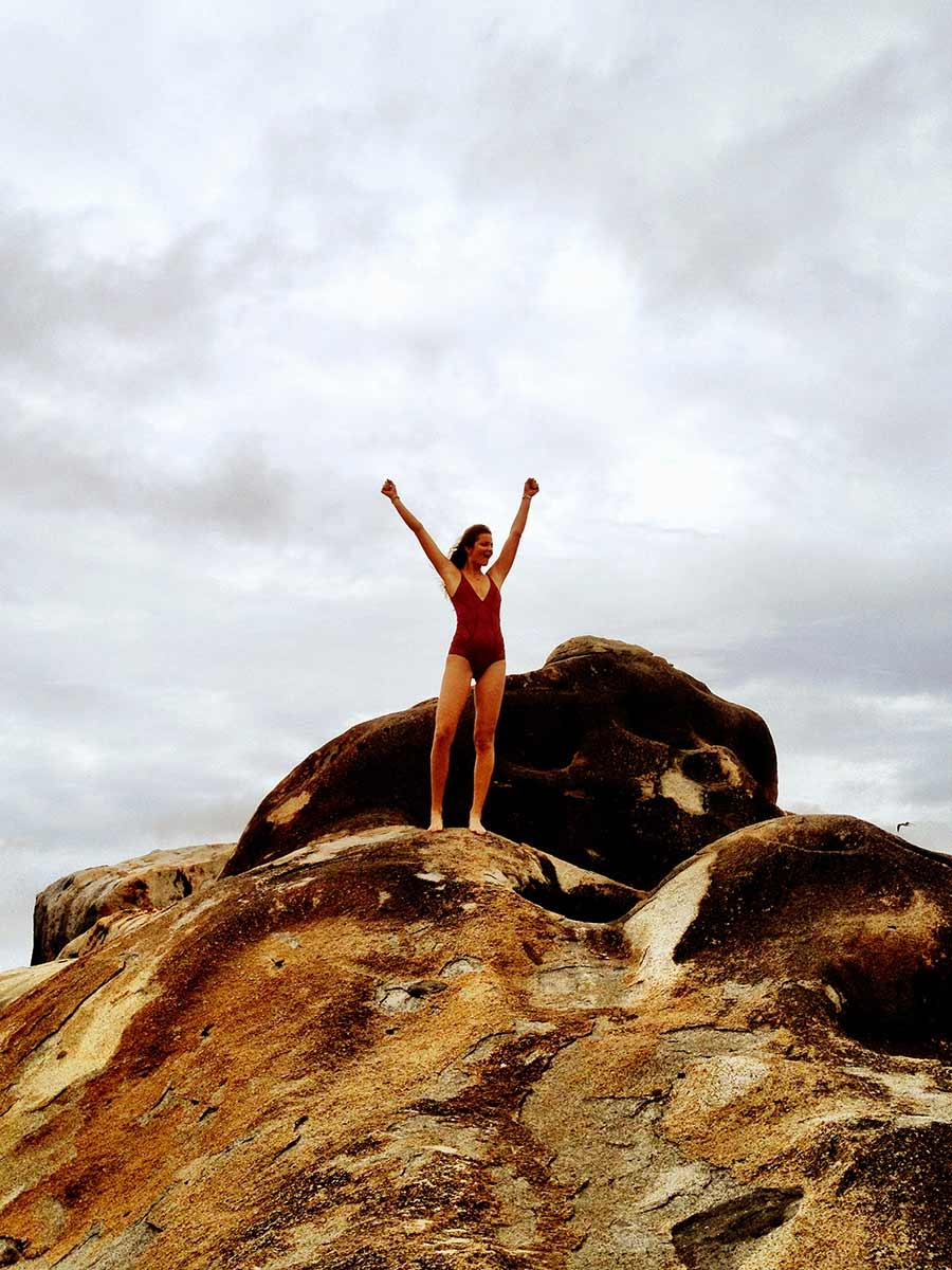 Our model stands on top of a rock with her hands in the air