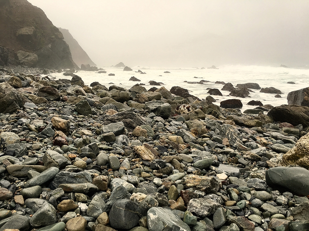 A rocky shore and whitewashed water sits underneath a hazy cloud