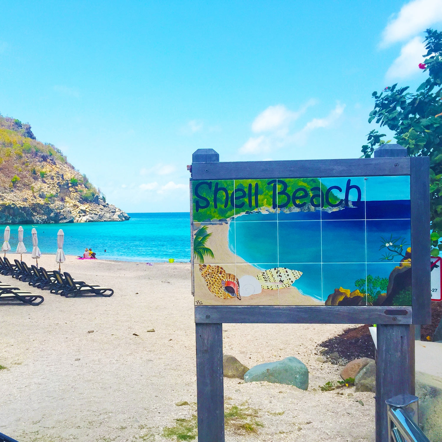 "A bright blue sign, reading ""Shell Beach"", painted with a rendition of the very beach set behind it"